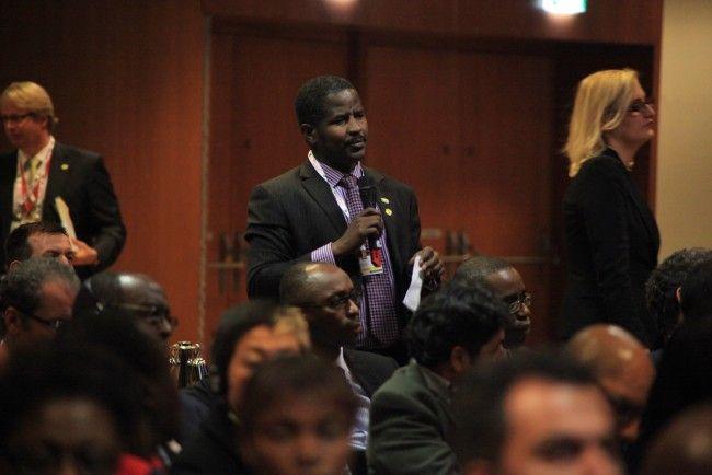 Bashir Gwandu, (standing and holding microphone)
