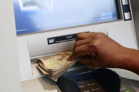 A woman takes Nigerian Naira from a bank's automated teller machine (ATM) in Ikeja district in the commercial capital Lagos
