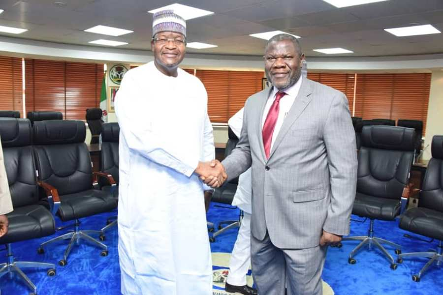 Professor Umar Garba Danbatta, Executive Vice Chairman and Chief Executive, NCC, left, in handshake with Nnamdi Nwokike, outgoing Director Public Affairs, NCC.