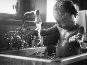 Black and white photograph of a naked baby playing joyfully while being bathed in a kitchen sink, taken by Laurie Rhodes