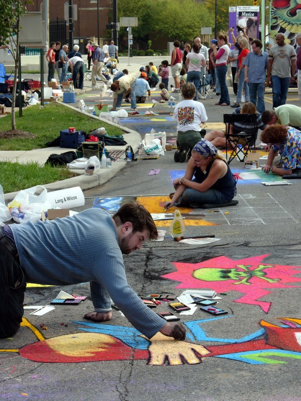 Onlookers watch artists at work along the Scioto Mile.