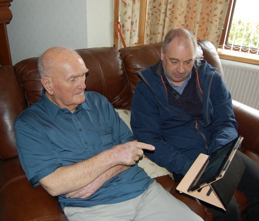 Picture of Iain Macleod showing a customer the tablet.