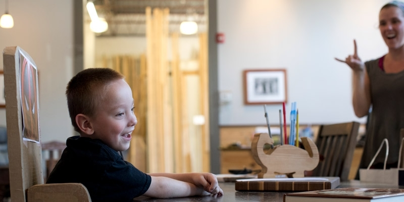 smiling boy sitting in an adapted chair made of cardboard