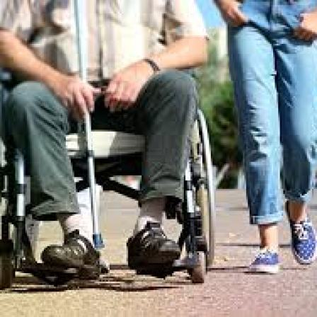 photo of the legs of a person in a wheelchair with a white cane and another person walking