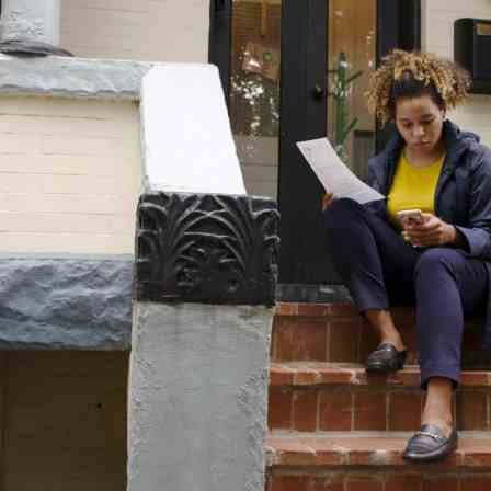 woman sitting on stoop looking at the census paper