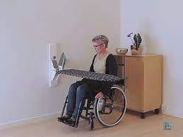 Woman in a wheelchair using wall mounted ironing board