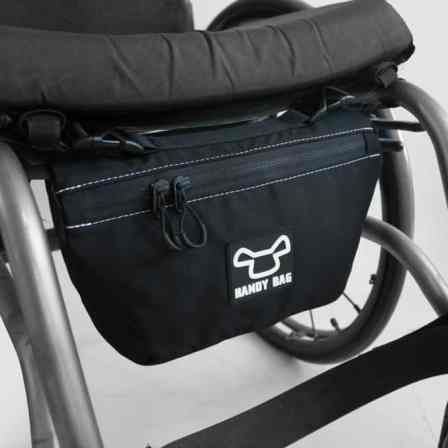 Close up of a zippered bag mounted under a wheelchair seat.