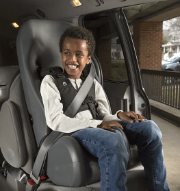 Boy sitting in a contoured foam car seat with harness and shoulder belt.