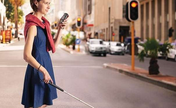 Woman with a white cane crosses a street holding a Trek audio device.