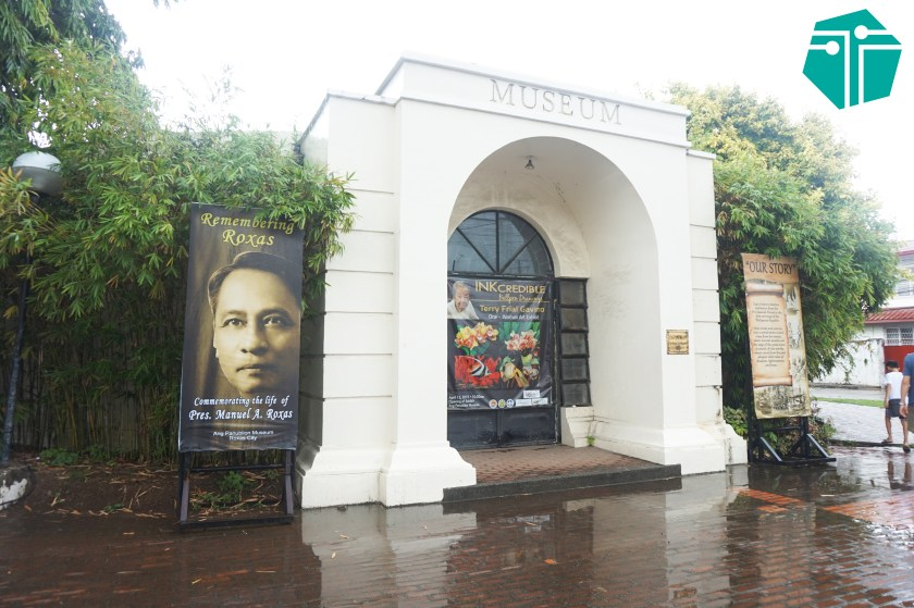 "A photo of the Panublion Museum facade with a ""Remembering Roxas"" poster on the left side. This was taken during our Capture Capiz and Iloilo Tour."