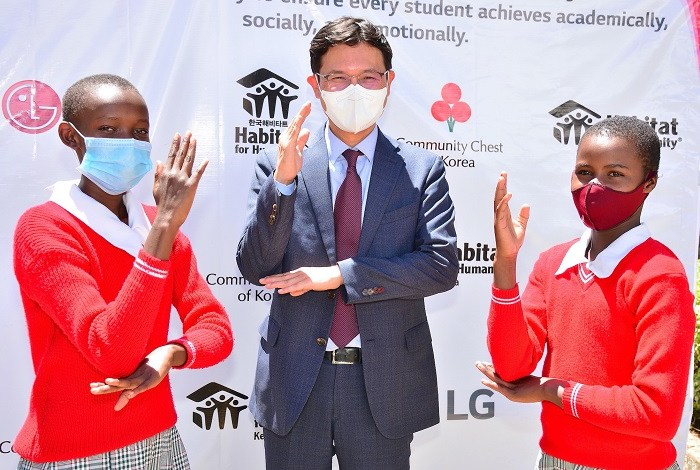 LG Electronics Managing Director for East and Central Africa, Sa Nyoung Kim (centre) is joined by Kanini Mbondo and Magdalene Kamene, class six pupils at the Machakos School for the Deaf.