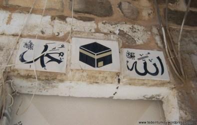 A bejárat feletti felirat hirdeti, hogy az itt lakó megjárta a mekkai zarándokutat (Mardin)