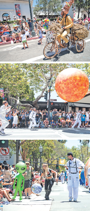 A spacey bicyclist waves to the crowd. Astronauts play with a giant ball. A little green man teases the crowd with some help from an astronaut.