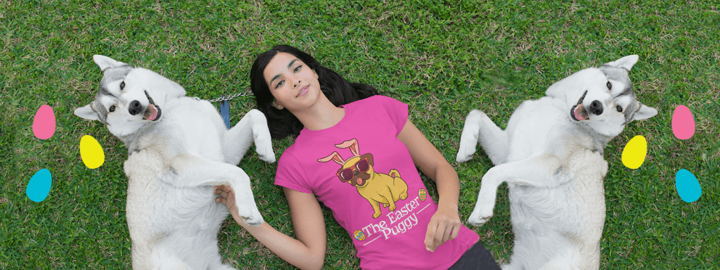 Girl laying on the grass using a sprint shirt design with two dogs