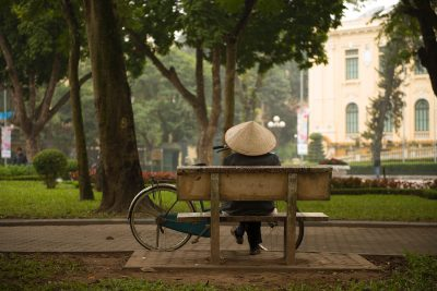 Woman sitting on park bench in Hanoi.
