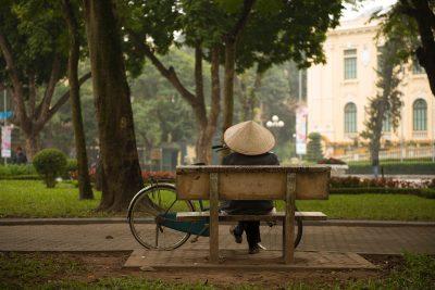 Woman sitting on park bench in Hanoi.