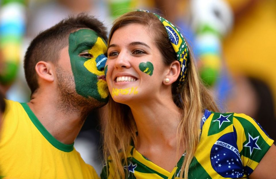 Brazilian couple kissing during football match