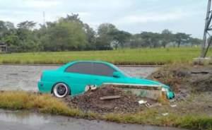 Mobil Sedan hijau yang terpeorosok di persawahan warga. FOTO : BISMA SURYA KURNIAWAN