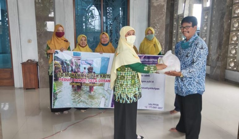 Kepala SD Muhammadiyah Kriyan Muntiasih ( kiri) memberikan bantuan kepada ketua PRM Dorang