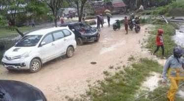 Anggota Polri bersdama warga membuat jalan alternatif yang putus akibat hujan. FOTO : MIRDAT