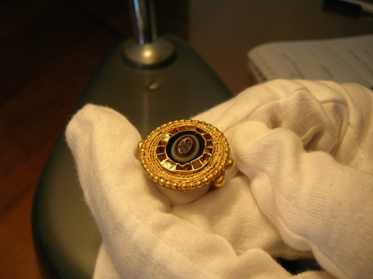 In this scene I examine a finger ring, reusing a late Roman agate seal, from southern Italy, late 7th century in the Museo Nazionale Archeologico di Napoli. In the next scene, the custodian of the stores tried it on and asked if it suited her (not pictured).