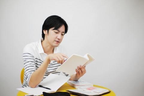 休日に資格試験の勉強をする男性。