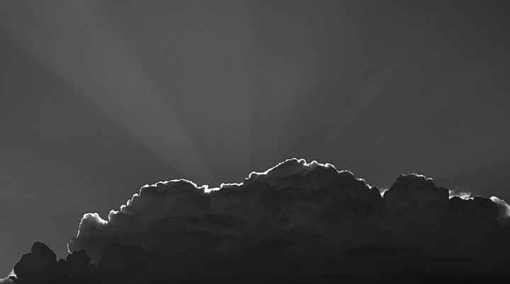 sun rays piercing through gray clouds