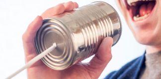 Persona hablando por un frasco de lata y cuerda