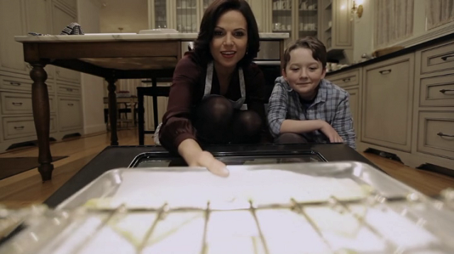 regina mills (played by lana parrilla) and owen flynn (played by benjamin james stockham) look into an oven
