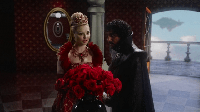 a screencap of the red queen (played by emma rigby) and jafar (played by naveen andrews) hanging out with some roses