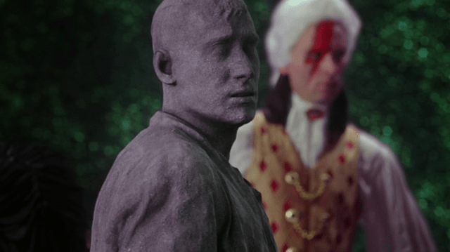 a screencap of the knave of hearts (played by cgi) turned to stone with a tweedle behind him
