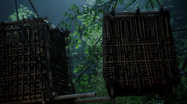 a screencap of two cages,one of which holds neal and the other holds a mystery person