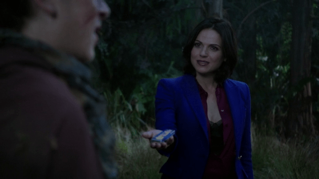 a screencap of regina (played by lana parrilla) offering a chocolate bar to devin (played by skyler gisondo)
