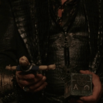 a screencap of rumpelstiltskin (played by robert carlyle) holding his doll and pandora's box