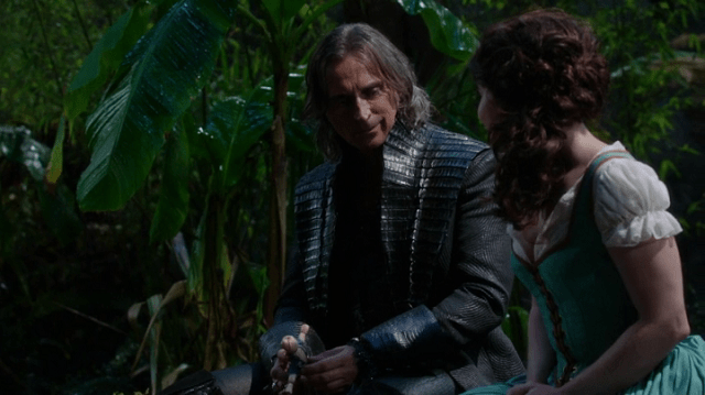 a screencap of rumpelstiltskin (played by robert carlyle) talking to an imposter belled (played by emilie de ravin)