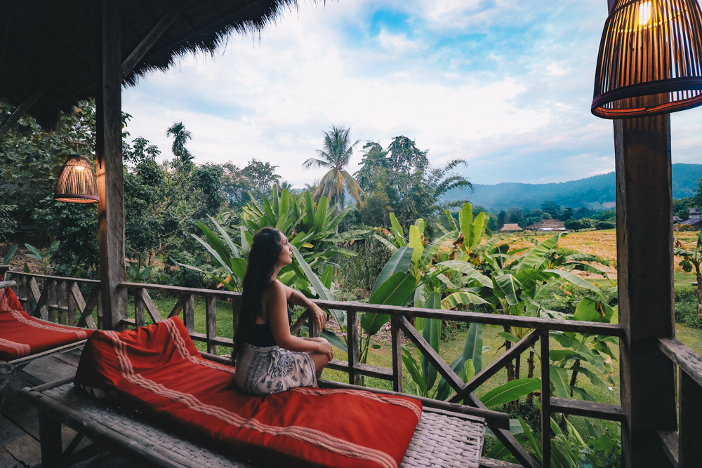 Lauren sits in Lisu Lodge by Asian Oasis: Where to stay in Chiang Mai Thailand for beautiful views