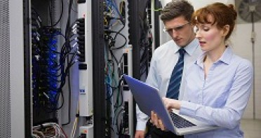 A woman and man looking at a laptop in a room with server racks