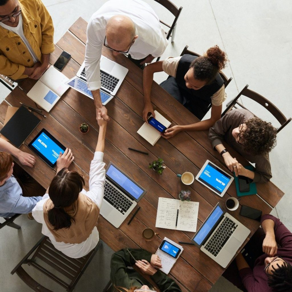 Overhead view of multiple people at a work table with two people shaking hands
