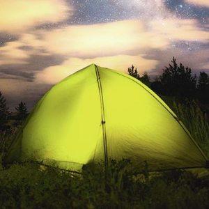 grønt pop up telt ude på åben mark i flot aften himmel
