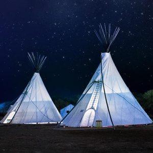 to hvide tipi telte som står på en dejlig sommer aften