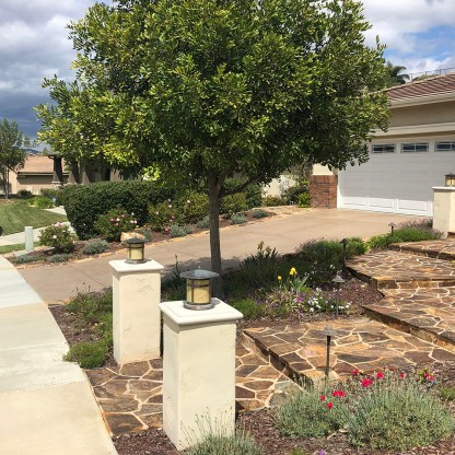 Traditional front yard with stonework and plantings