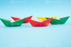 Colorful origami paper boats on blue