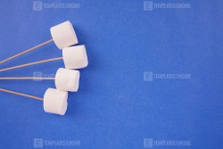 White marshmallows with sticks on blue background