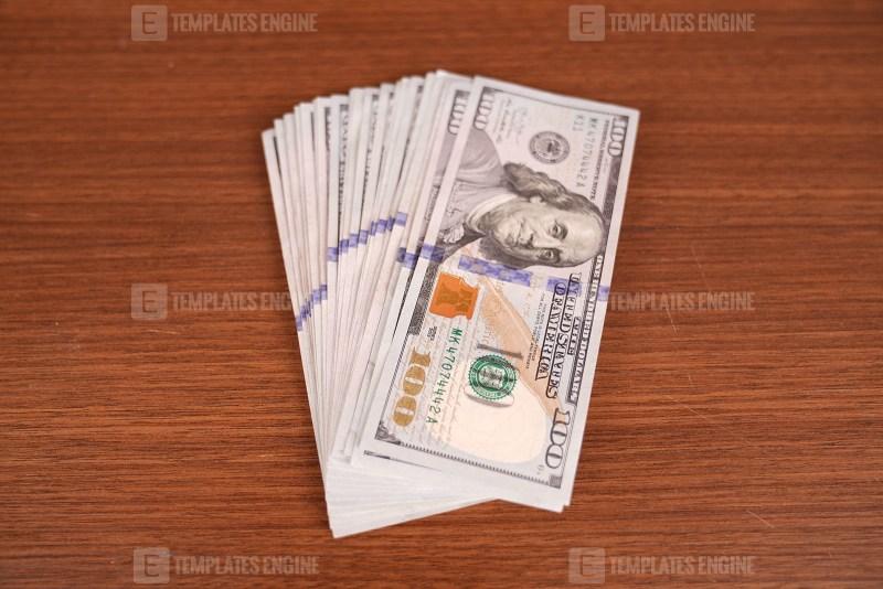 Dollar bills on wooden surface