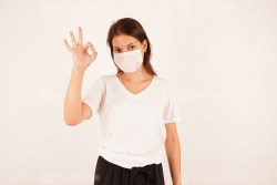 Woman in medical mask showing OK gesture
