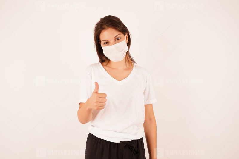 Woman in medical mask showing shows thumb up