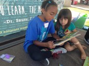 anna reading to younger kid_ib