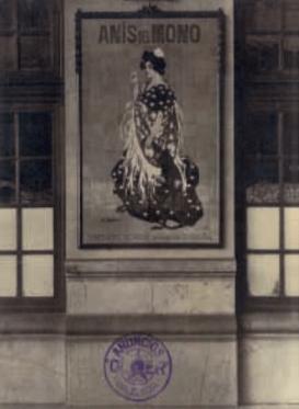 """Fotografia de la casa """"Anuncios Oliver"""" con un cartel cerámico de la fábrica Valencia Industrial que reproduce el original de Ramón Casas """"Anís del Mono"""". Andanes de la Estación del Norte de Valencia, c. 1920"""