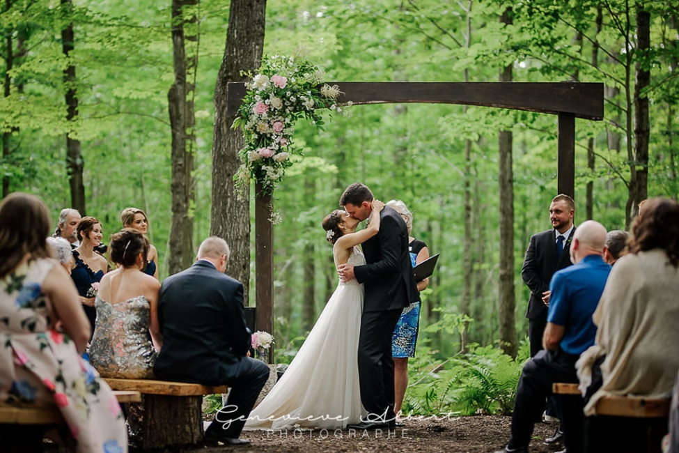 Bridge and groom under arch in forest wedding venue
