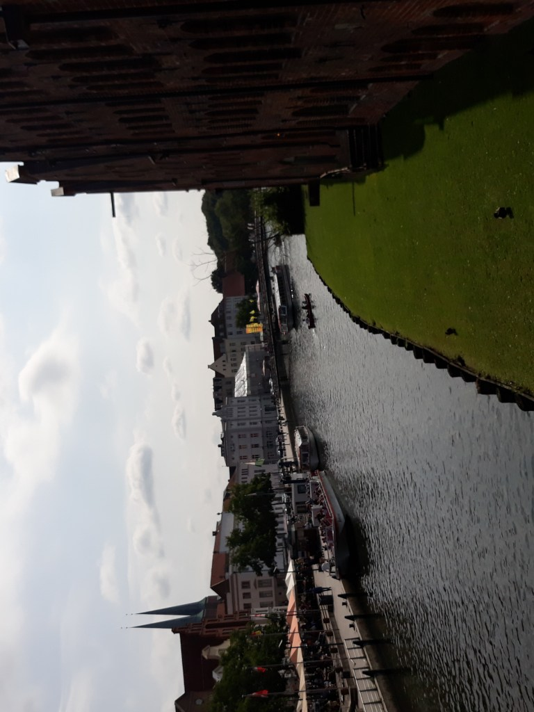 The following image shows the river known as the Trave, which flows around the northern German city, Luebeck. To the right is a large, brick building which once served as the city's gate. To the left of the river are white houses and restaurants.